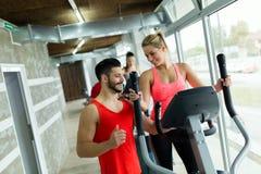 Mujer atractiva que trabaja ejercicios cardiios con el instructor Fotos de archivo