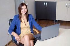 Mujer atractiva que trabaja en el ordenador portátil en oficina de lanzamiento imagenes de archivo