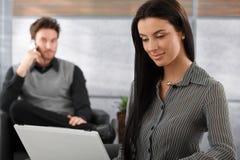 Mujer atractiva que trabaja en la sonrisa de la computadora portátil Fotos de archivo