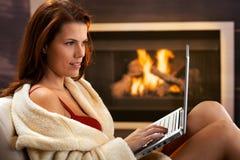 Mujer atractiva que usa el ordenador en invierno Imagenes de archivo