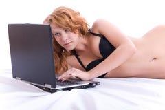 Mujer atractiva que usa el ordenador portátil. Imagen de archivo libre de regalías