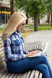Mujer atractiva que usa el ordenador portátil en banco en parque Imagen de archivo