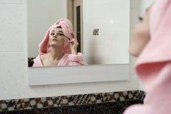 Mujer atractiva que usa el rimel mientras que mira en espejo Fotos de archivo libres de regalías