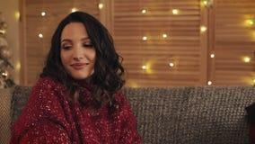 Mujer atractiva que usa el smartphone que se sienta en el sofá, mensajería, sonriendo en el apartamento adornado cerca de agradab almacen de video