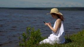 Mujer atractiva que usa el teléfono móvil en la orilla, agua azul profunda en fondo Foto de archivo