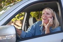 Mujer atractiva que usa el teléfono celular mientras que conduce Fotografía de archivo libre de regalías