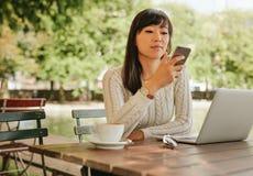 Mujer atractiva que usa smartphone en la cafetería Imágenes de archivo libres de regalías