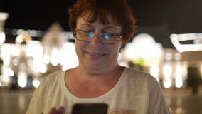 Mujer atractiva que usa un teléfono móvil mientras que camina a través de las calles en una ciudad de la noche, en la ciudad de l metrajes