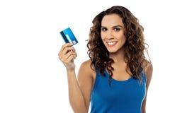 Mujer atractiva que visualiza su tarjeta de crédito fotos de archivo