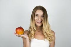Mujer atractiva rubia sonriente que sostiene la manzana roja jugosa en un fondo blanco aislado mano imagenes de archivo