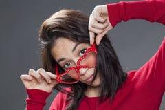 Mujer atractiva 20s que mira sobre sus vidrios del rojo de la diversión Fotos de archivo