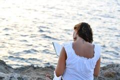 Mujer atractiva 40s que se sienta solamente en la playa que lee un libro Foto de archivo