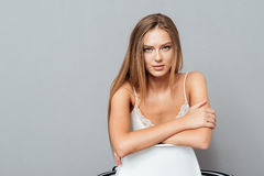 Mujer atractiva seria que se sienta en la silla Imagen de archivo libre de regalías