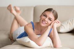 Mujer atractiva sonriente de los jóvenes que miente en el sofá que mira la cámara Imagen de archivo