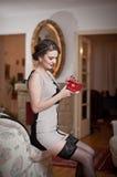 Mujer atractiva sonriente feliz que lleva un vestido elegante y medias negras que sientan en la tenencia de brazo del sofá una pe Fotos de archivo libres de regalías