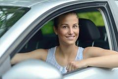 Mujer atractiva sonriente que conduce un coche Imagen de archivo libre de regalías