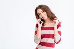 Mujer atractiva sonriente que habla en el teléfono Imágenes de archivo libres de regalías
