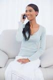 Mujer atractiva sonriente que se sienta en el sofá acogedor que tiene un teléfono caloría Imagen de archivo