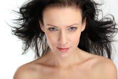 Mujer atractiva triguena hermosa con el pelo del vuelo en el fondo blanco Fotos de archivo libres de regalías
