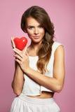 Mujer atractiva vivaz con un corazón rojo - celebraciones del día de tarjeta del día de San Valentín, de la boda, del compromiso  Imagenes de archivo