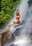 Mujer atractiva y feliz joven 30s con la corriente tropical inferior mojada practicante de la cascada del paraíso de la yoga del  fotografía de archivo
