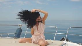 Mujer atractiva y rica joven que tiene fotosession en un barco de lujo en el mar almacen de video