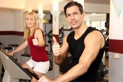Mujer atractiva y un hombre que completa un ciclo en un gimnasio Imagen de archivo libre de regalías
