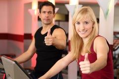 Mujer atractiva y un hombre que completa un ciclo en un gimnasio Imágenes de archivo libres de regalías