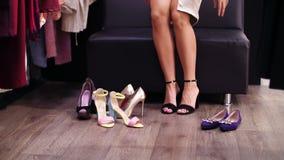 Mujer atractiva, zanquilarga que intenta en las sandalias de tacón alto negras en una tienda elegante, boutique Cámara lenta Prim