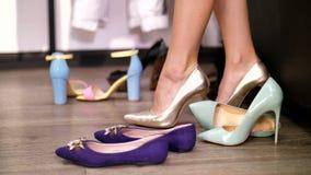Mujer atractiva, zanquilarga que intenta en los zapatos oro-coloreados en un talón de tacón alto en una tienda elegante, boutique almacen de video