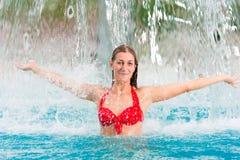 Mujer bajo el adminículo del agua en piscina Fotografía de archivo libre de regalías