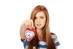 Mujer bastante adolescente con el despertador Imagenes de archivo