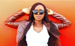 Mujer bastante africana en gafas de sol y chaqueta en la ciudad sobre rojo imágenes de archivo libres de regalías