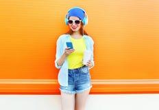Mujer bastante alegre con la taza de café usando smartphone sobre naranja colorida Fotografía de archivo