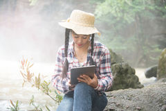 Mujer bastante asiática del viajero que mira una tableta Foto de archivo