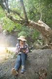Mujer bastante asiática del viajero que mira una tableta Imagenes de archivo