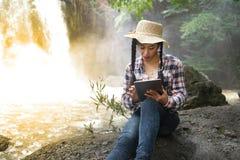 Mujer bastante asiática del viajero que mira una tableta Imágenes de archivo libres de regalías