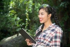 Mujer bastante asiática del viajero que mira una tableta Fotos de archivo libres de regalías