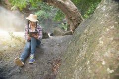 Mujer bastante asiática del viajero que mira una tableta Fotografía de archivo