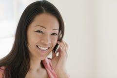 Mujer bastante asiática en el teléfono celular Imagenes de archivo