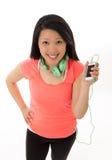 Mujer bastante asiática que escucha los auriculares de la música Fotos de archivo libres de regalías