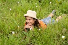 Mujer bastante asiática que miente en campo de flor. Foto de archivo