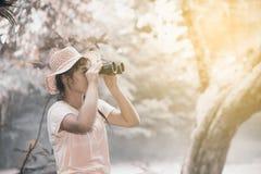 Mujer bastante asiática que mira con los prismáticos Fotos de archivo libres de regalías