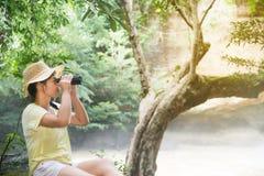Mujer bastante asiática que mira con los prismáticos Fotos de archivo