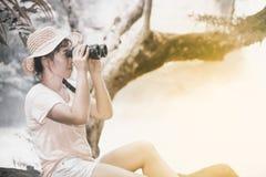 Mujer bastante asiática que mira con los prismáticos Fotografía de archivo