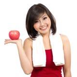 Mujer bastante asiática que muestra una manzana en su mano Imágenes de archivo libres de regalías