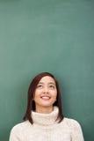 Mujer bastante asiática que se coloca que sueña despierto Imagen de archivo libre de regalías