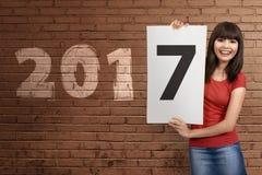 Mujer bastante asiática que se sostiene de papel con los números 7 en la pared 2017 Foto de archivo