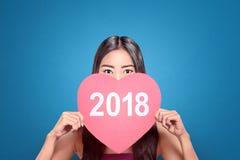 Mujer bastante asiática que sostiene el papel del corazón con el número 2018 Fotos de archivo libres de regalías