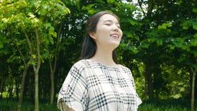 Mujer bastante asiática que toma la respiración profunda, sonriendo y disfrutando de la naturaleza al aire libre almacen de metraje de vídeo
